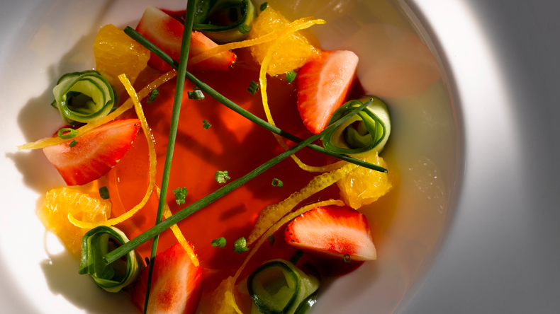 Summer dessert of Pimms jelly, served with strawberries, candied orange zest, orange segments,  rolled up cucumber ribbons, chives and mint. Nominated in the International Color Awards